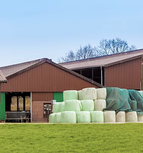 two large metal farm sheds with bales of hay wrapped in plastic stored in front of them.