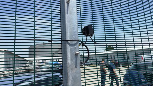 A close up shot of a motion sensor attached to a large metal fence.