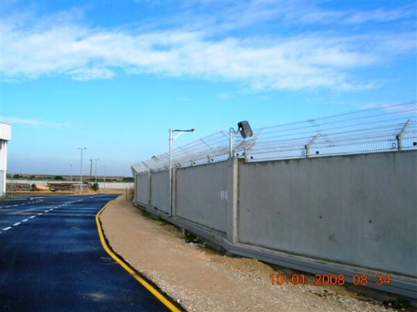 A anti clib fence mounted on top of a wall, the fence has a detection system mounted to it.