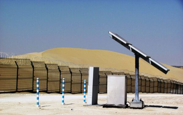 A perimeter fence in some sand dunes with a detection system mounted to it. protecting a solar panel array.