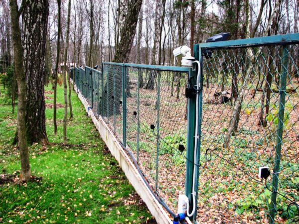 A perimeter fence with a detection system mounted to it. there is also a CCTV camera mounted