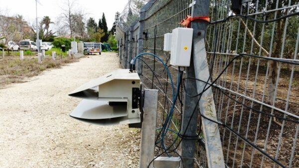 A laser detection system from the side mounted to a metal fence.