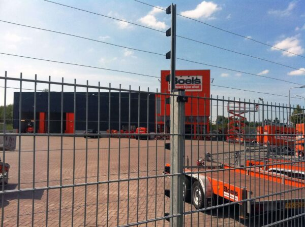 POWER-SENS security system mounted on a metal security fence protecting a commercial site.