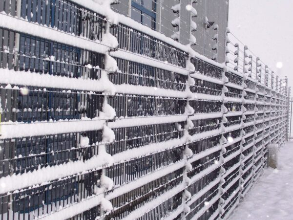 POWER-SENS security system mounted on a metal security fence covered in snow