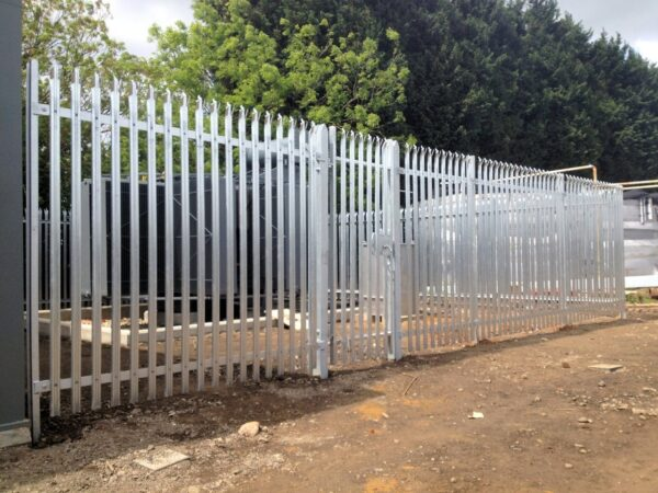 A metal palisade fence protecting an electrical instalation.
