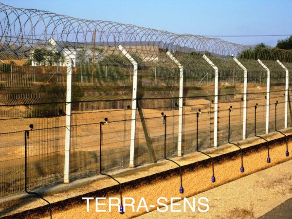 A perimeter fence with a Tera Sens motion sensor detector kit mounted to it.