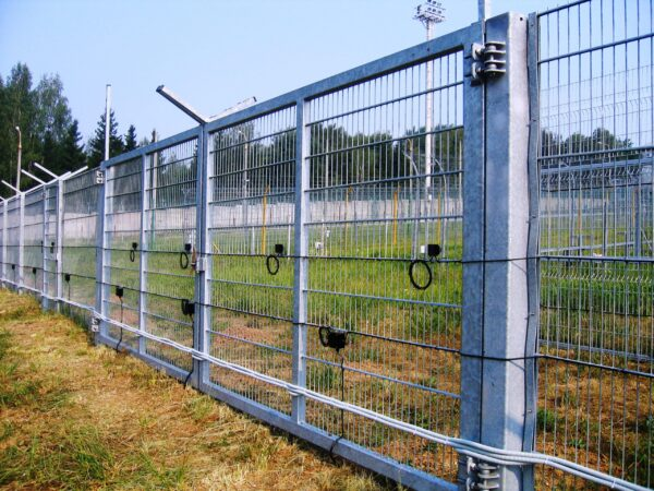A perimeter fence with a motion sensor detector kit mounted to it.