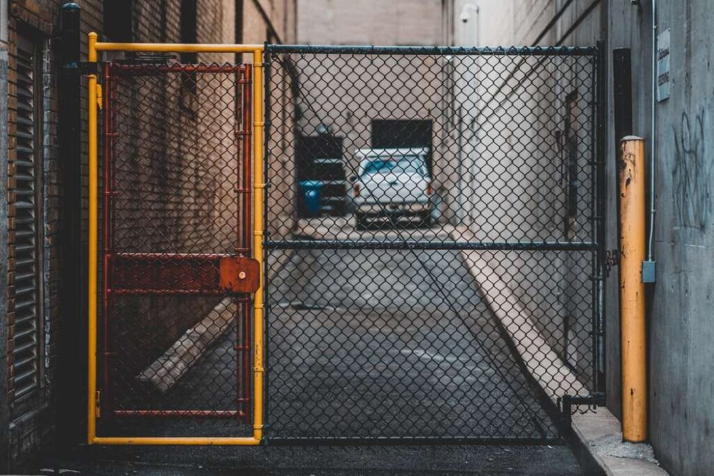 Side entrance gate to a production facility with yellow gate, post and a chain link fence