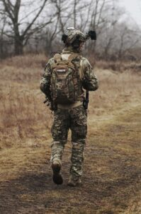 A lone soldier walking along a field path viewed from behind