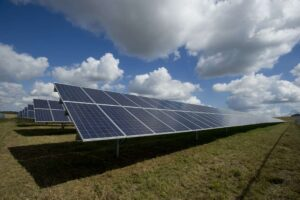 Images of solar panels in a field with a blue and white clouded sky