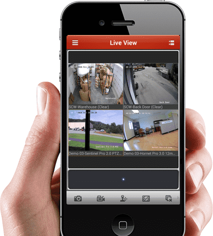 A hand holding a phone with multiple CCTV feed on the screen