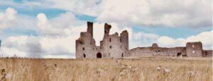 A derelict castle in a corn field.